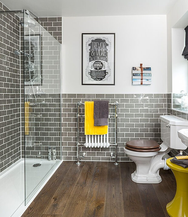 Grey Bathroom With Yellow Towel and Stool
